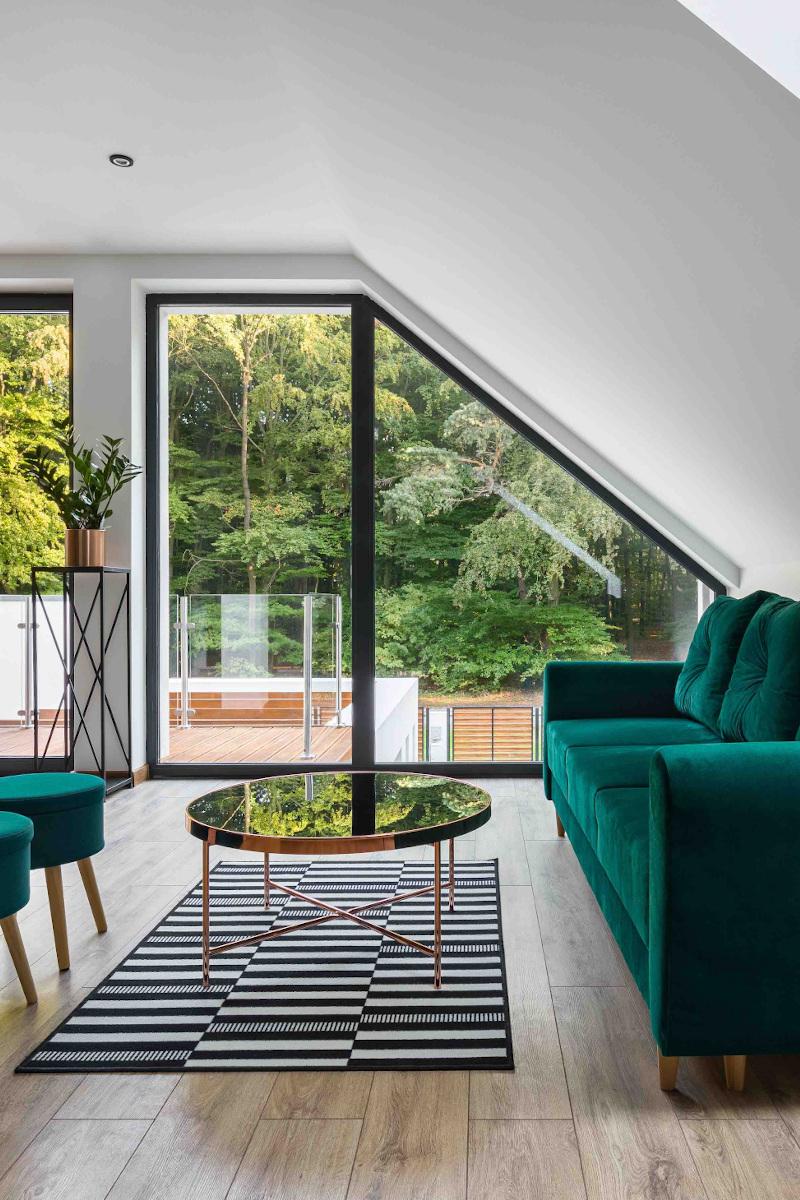 Wohnzimmer in einem Dachgeschoss mit grünem Sofa