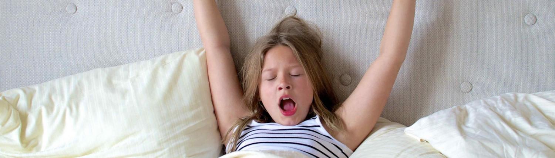 Mädchen liegt gähnend im Bett