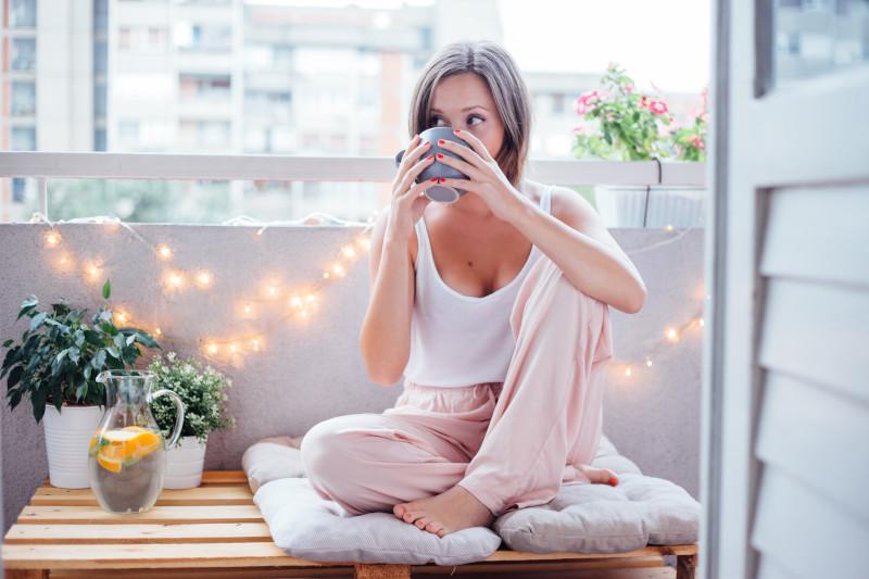 Frau trinkt Kaffee auf Balkon