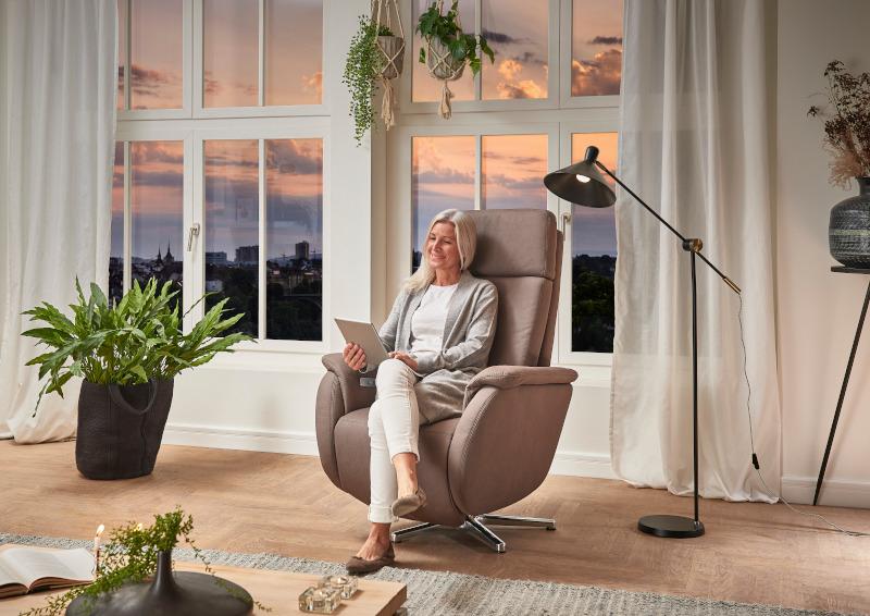 Sessel in beige vor einer großen weißen Fensterfront