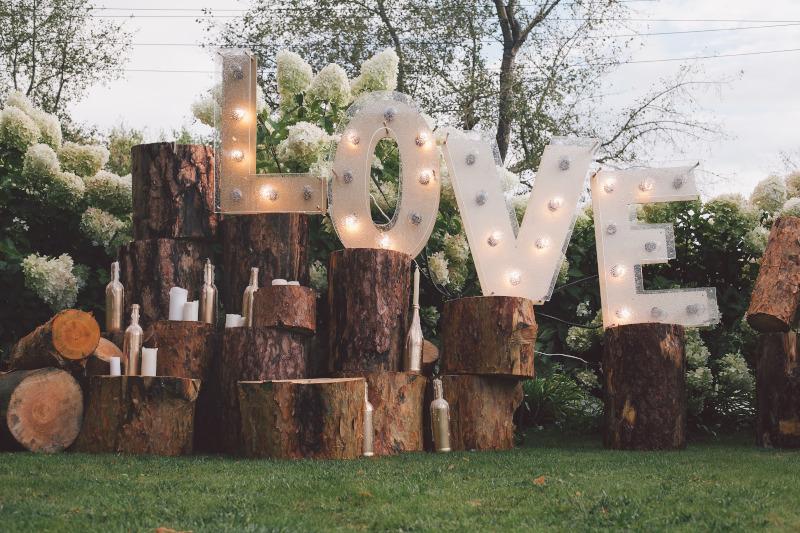 Deko mit Baumstämmen und Love Schriftzeichen und Kerzen