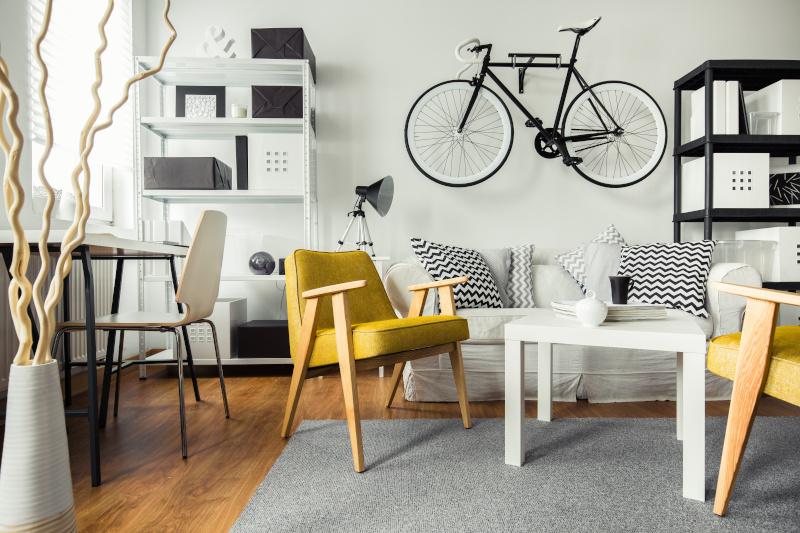 Einzimmerwohnung mit gelben Stühlen und weißer Couch und Fahrrad an der Wand