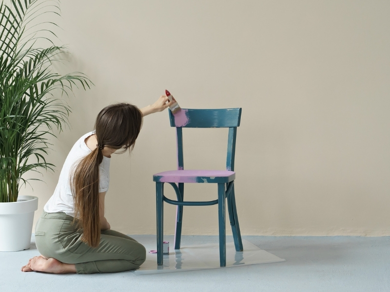 Frau bemalt Stuhl in lila